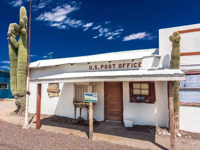 A little white post office that appears to be boarded up;  a cactus stands in front of it